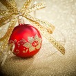 Christmas ball with golden ribbon - Stock Photo
