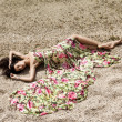 Girl lying on the sand by the sea — Stock Photo