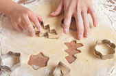 Little girls and mother cutting cookies, hands only — Stock Photo