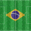 Brazilian flag on  a soccer field — Stock Photo