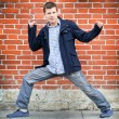 Royalty-Free Stock Photo: Active young man posing over grunge brick wall