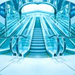 Business hall with blue vanishing escalators — Stock Photo