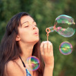 Pretty woman inflating soap-bubbles - Stock Photo