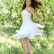 Beautiful young woman dancing in the morning bright summer orchard — Stock Photo