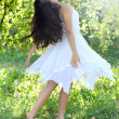 Beautiful young woman dancing in the morning bright summer orchard — Stock Photo #16959475