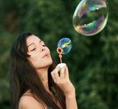 Bella donna gonfiare bolle di sapone — Foto Stock