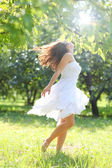 Adorable young girl in white clothes enjoying barefooted over morning dew of summer park — Stock Photo
