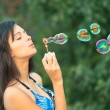 Portrait of attractive young girl inflating colorful soap bubbles in nature - Stock Photo