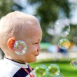 Happy child inflating soap bubbles — Stock Photo
