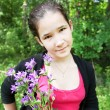 Happy young girl with brigth bluebell flowers in beautiful bunch — Stok fotoğraf