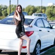 Beautiful young woman standing near white sport car and talking by phone — Stock Photo
