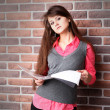 Smiling young business woman with document over brickwall — Stock Photo