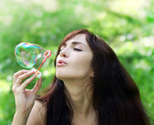 Adorable young girl inflating colorful soap bubbles in summer pa — Stock Photo