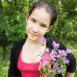 Happy young girl with brigth bluebell flowers in beautiful bunch - Stock fotografie