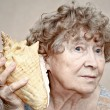 Smiling great grandmother listening to a seashell — Stockfoto