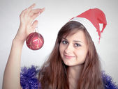 Attractive young girl with christmas presents wondering — Stock Photo