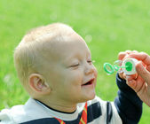 Happy child inflating soap bubbles — Stockfoto