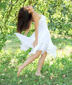 Beautiful young woman dancing in the morning bright summer orcha — Stock Photo