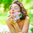 Romantic young girl laying and inflating colorful soap bubbles i — Stock Photo