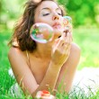 Romantic young girl laying and inflating colorful soap bubbles i — Stock Photo #18695791