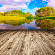 Light picturesque scene of beautiful rural lake in sunny summer park over blue sky with first dawn rays on the wall inside room interior with frame textured wooden brown panel floor background — Stock Photo #18697403