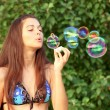 Girl inflating colorful soap bubble — Stock Photo