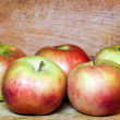 Composition of sappy juicy red apples over grungy domestic woode — Stock Photo #25208551