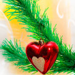 Red heart hanging on Christmas fir tree — Stock fotografie