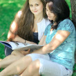 Mother and daughter reading book in park — Zdjęcie stockowe