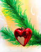 Red heart hanging on Christmas fir tree — Stock Photo
