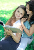 Mother and daughter reading book in park — Foto Stock