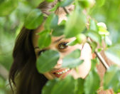 Woman concealing in summer park — Stock Photo