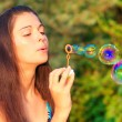 Woman inflating soap-bubbles — Stock Photo