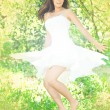 Young woman dancing in the orchard — Stock Photo