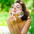 Girl inflating colorful soap bubbles — Stock Photo #25380053