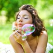 Girl inflating colorful soap bubbles — Stock Photo #25380133