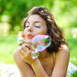Girl inflating colorful soap bubbles — Stock Photo