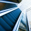 Wide angled view to perspective escalators stairway inside contemporary blue glass business centre, concept of successful career elevation — Stock Photo #25386997