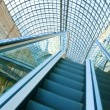 Wide angled view to perspective escalators stairway inside contemporary blue glass business centre, concept of successful career elevation — Stock Photo #25387015
