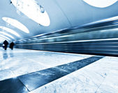 Perspective wide angle view of modern light blue illuminated and spacious public metro marble station with fast blurred trail of train in vanishing traffic motion — Stock Photo