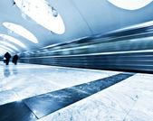 Large angle de perspective découvre moderne lumière bleue lumineuse et spacieuse publique station de métro en marbre avec rapide piste brouillée de train en voie de disparition mouvement de trafic — Photo
