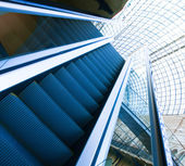 Wide angled view to perspective escalators stairway inside contemporary blue glass business centre, concept of successful career elevation — Stock Photo