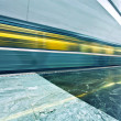 Stock Photo: Perspective wide angle view of modern light blue illuminated and spacious public metro marble station with fast blurred trail of train in vanishing traffic motion