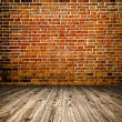Empty red old spacious room with stone grungy wall and wooden weathered dirty floor, vintage background texture of brickwall — Stock Photo