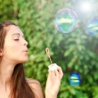Pretty woman inflating soap-bubbles — Stock Photo #25427907