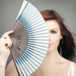 Portrait of mysterious woman hiding behind retro fan — Stock Photo #25425697