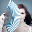 Royalty-Free Stock Photo: Portrait of mysterious woman hiding behind retro fan