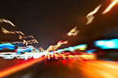 Perspective and panoramic wide angle view of modern light blue illuminated and spacious high-speed urban road and moving cars with fast blurred trail of headlights in vanishing traffic motion at night — Stock Photo