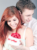 Lovely couple surprising with red gift box — Zdjęcie stockowe