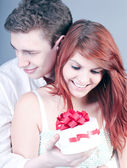 Lovely couple surprising with red gift box — Stock Photo